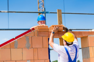 Bricklayer or builders on construction site working